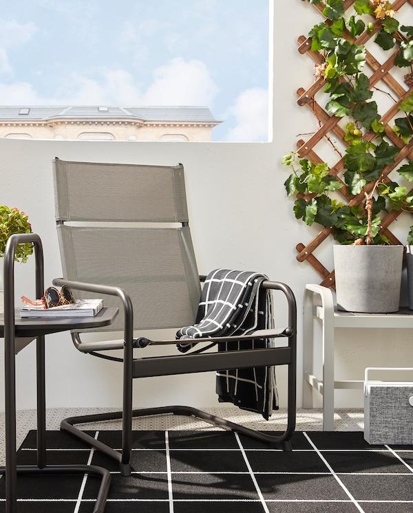 HUSARÖ fotel és kisasztal, sötétszürke színben, egy fekete/fehér szőnyegen az erkélyen. Mellette pad, szürke kaspóval.