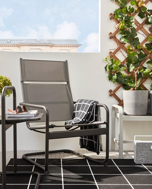 HUSARÖ lænestol og sofabord i mørkegråt står på et sort/hvidt tæppe på en altan. Ved siden af står en bænk med en grå urtepotteskjuler.