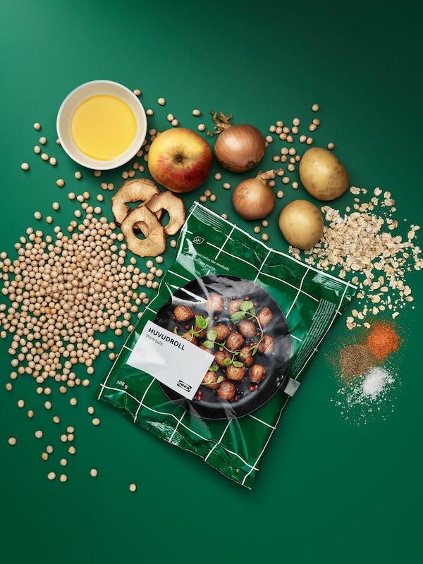 ห่อบอลผัก HUVUDROLL มีวัตถุดิบที่ยังไม่ได้ทำเป็นอาหารวางอยู่รอบ ๆ ได้แก่ ถั่ว ข้าวโอ๊ต มะเขือเทศ หัวหอม แอปเปิ้ล เครื่องเทศ