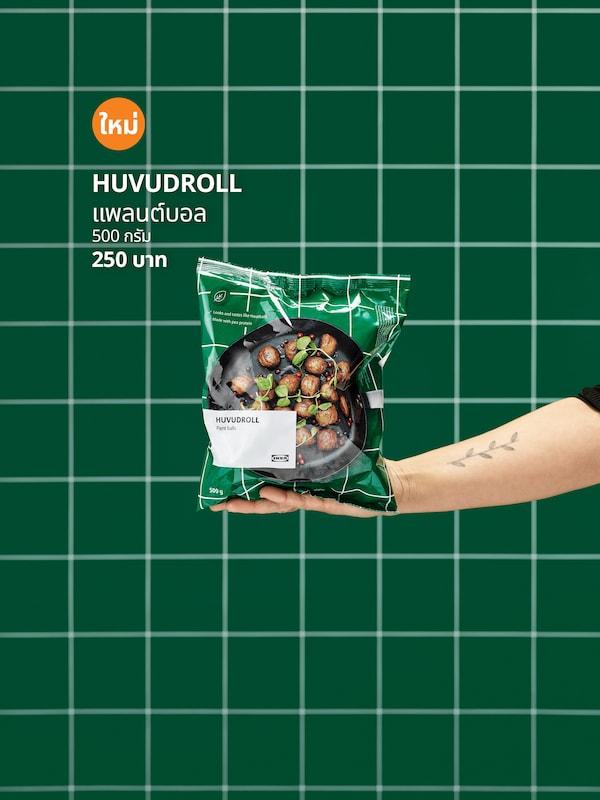 มือที่ยืนมา ในมือถือห่อบอลผัก HUVUDROLL ที่ยังไม่ได้เปิด พื้นหลังเป็นผนังกระเบื้องสีเขียว