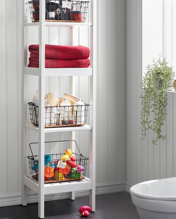 Hvid HEMNES reol med sorte PLEJA trådkurve med håndklæder, badelegetøj, spa-udstyr og meget andet på de 4 hylder.