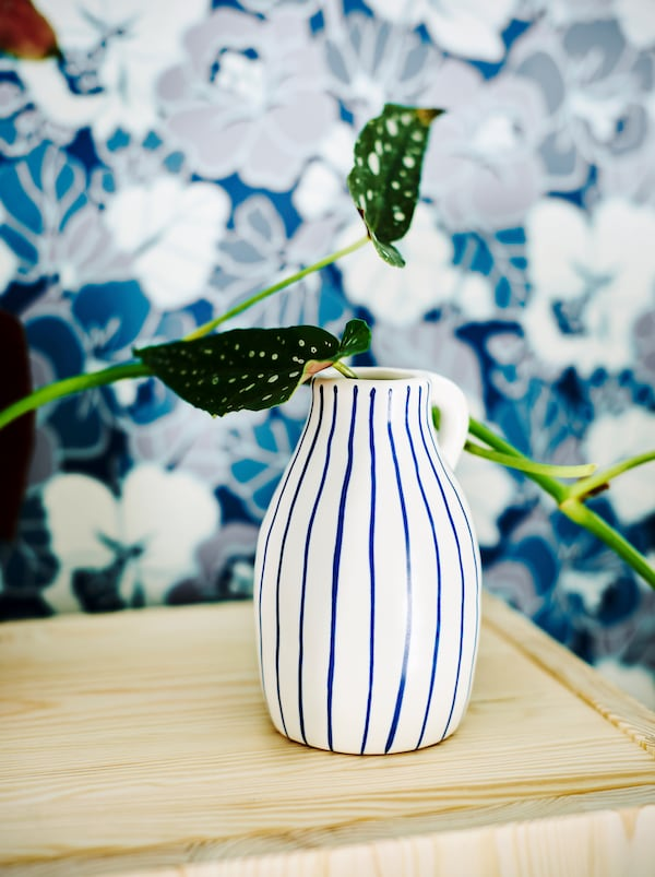 Hvid keramikvase med uregelmæssige blå striber med en plante står foran tapet med et blåt og hvidt blomstermønster.