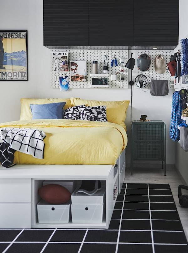 Hvid PLATSA seng i et værelse med klatreudstyr og ungdommeligt tilbehør på vægmonterede SKÅDIS hulplader.