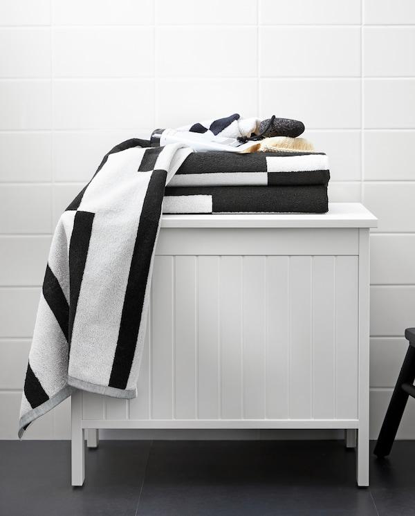 Hvid SILVERÅN opbevaringsbænk med håndklæder med et grafisk sort og hvidt mønster står på et badeværelse.