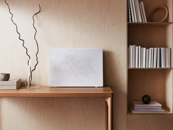 Hvid SYMFONISK billedramme med wi-fi-højttaler er udstillet på et bord med en vase ved siden af en reol.