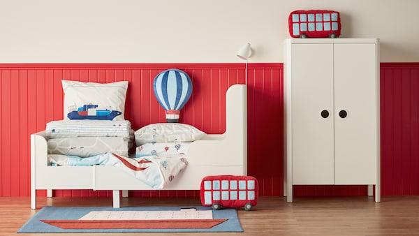 Hvide børnemøbler fra BUSUNGE serien – et garderobeskab og en børneseng, der står på et trægulv op ad et rødt panel.