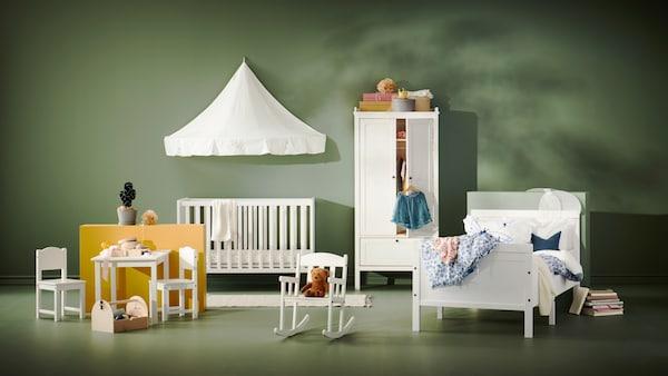 Hvide børnemøbler, herunder et borde-/stolesæt, udtræksseng, tremmeseng og en gyngestol fra SUNDVIK serien.