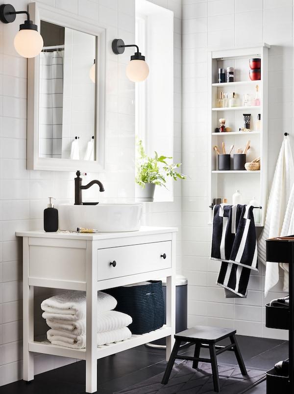 Hvide HEMNES badeværelsesmøbler med en skuffe, en hylde med håndklæder, et HAMNSKÄR blandingsbatteri, et spejl og 2 lamper.
