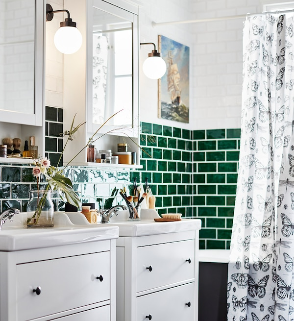 Hvide vaskeskabe med skuffer i et grønt badeværelse.