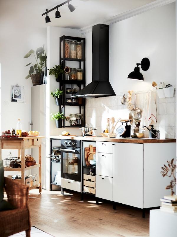Hvidt og sort køkken med varme toner fra gulvet, køkkenbordet og et FÖRHÖJA rullebord af træ.