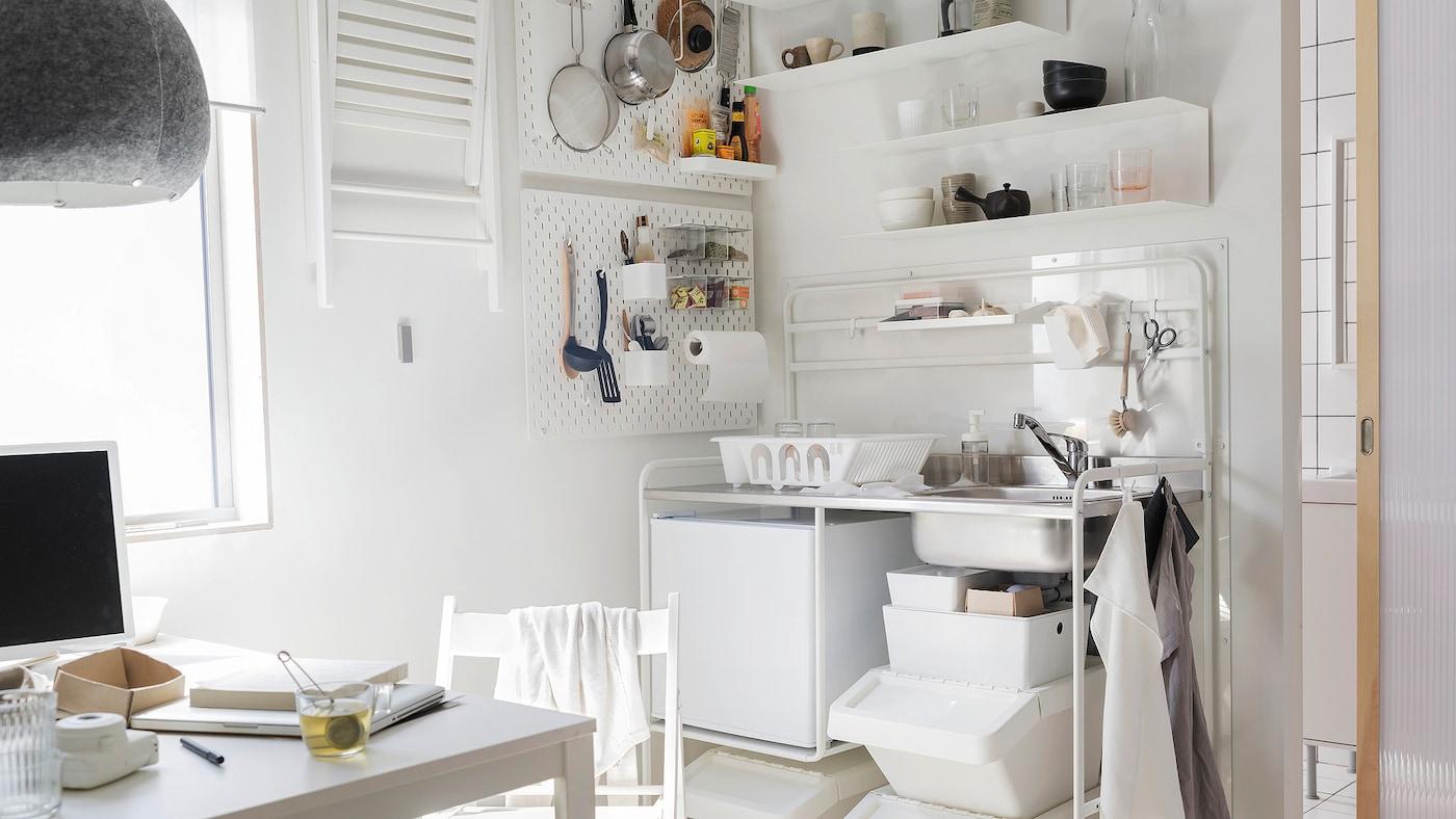 Hvit kjøkkenkrok med SUNNERSTA minikjøkken, et lite kjøleskap, bord og stol, alt sammen i hvitt.