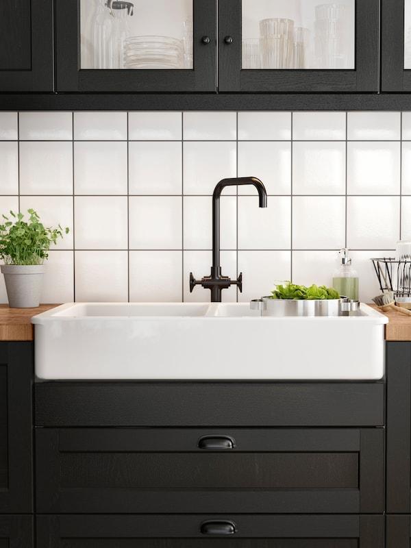 Hvit oppvaskkum med synlig front og blandebatteri av svart børstet metall i et kjøkken med svartbeisede trefronter.