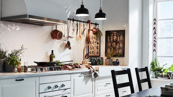Hvitt kjøkken med tradisjonelle BODBYN dører og skuffefronter opplyst av to svarte taklamper.