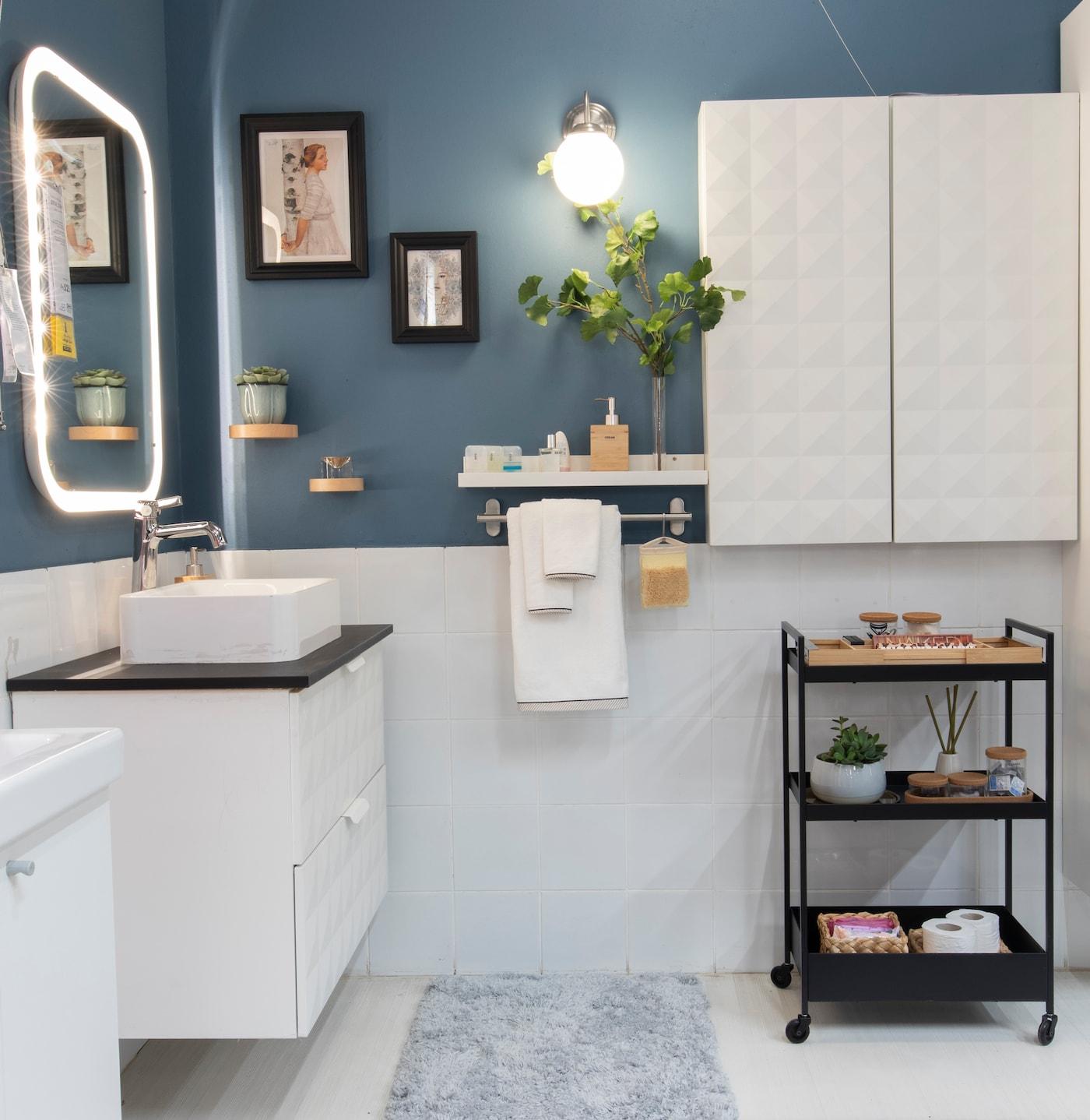 حوض وحنفية على جدار أزرق، مع مرآة وإضاءة.