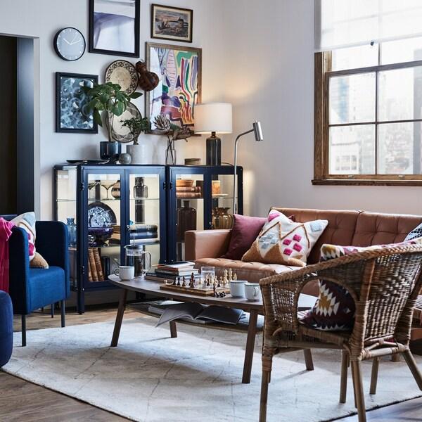 Hyggelig stue med kurvemøbler og vitrineskabe