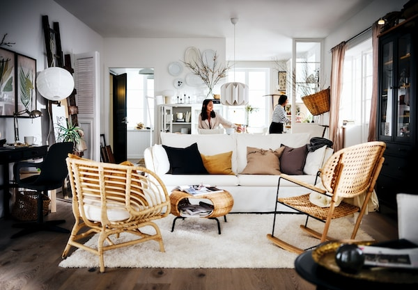 Hyggelig stue med sofaer, fletstol, vitrineskab og et lækkert blødt tæppe.