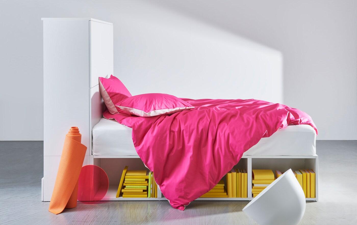 هيكل سرير أبيض مع تخزين مدمج مع مفارش سرير وردي.