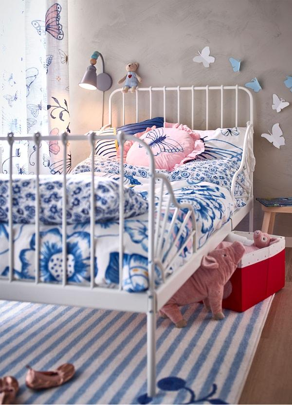 هيكل سرير أبيض قابل للتمديد MINNEN من ايكيا ومفارش سرير SÅNGLÄRKA أزرق وأبيض فراشات.