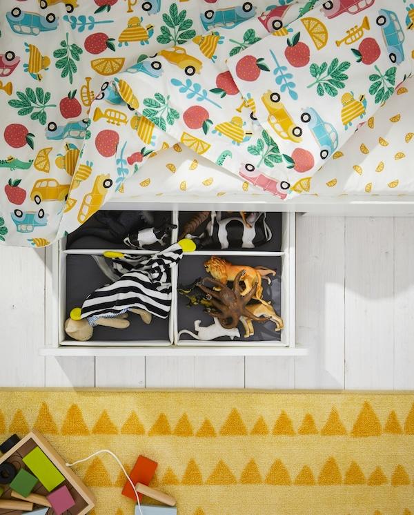 هيكل سرير بدرج مفتوح به ألعاب، وسجادة صفراء، وغطاء لحاف ملون وشرشف سرير أبيض/أصفر.