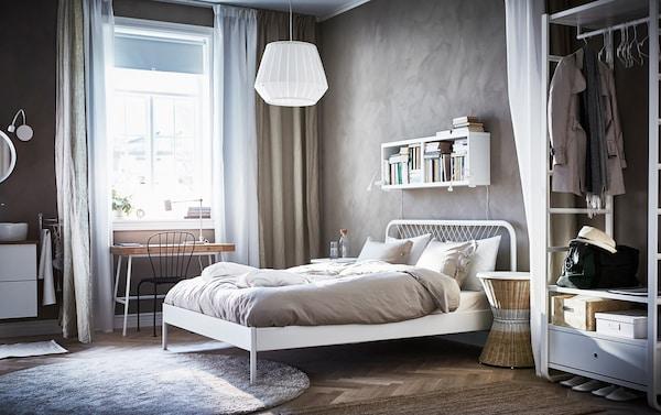 هيكل سرير سلكي أبيض على الطراز الاسكندنافي NESTTUN من ايكيا في غرفة ذات جدران بيج جميلة ودولاب ملابس مفتوح.