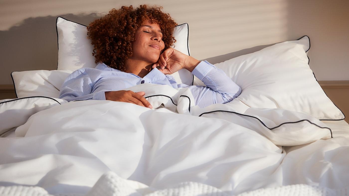 Hymyilevä, kiharahiuksinen nainen makaa silmät kiinni vaaleilla vuodevaatteilla pedatussa sängyssä peiton alla.