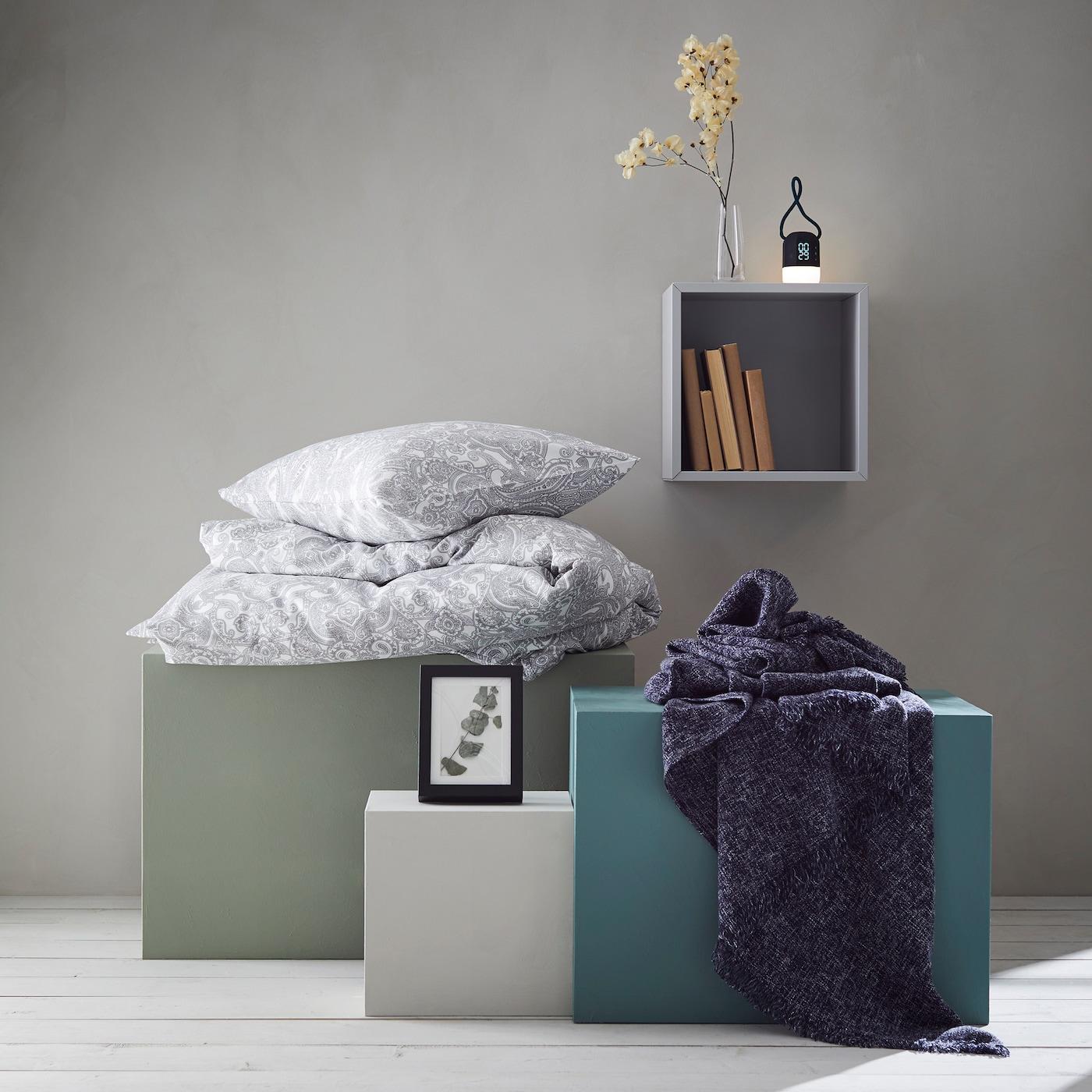 Hyvän unen setti JÄTTEVALLMO sisältää vaaleat paisley-kuvioiset vuodevaatteet, huovan, kuvakehyksen ja herätyskellon.