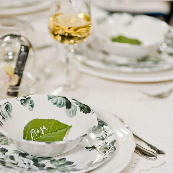 I en skål ligger ett grönt löv som placeringskort med handskrivet namn.
