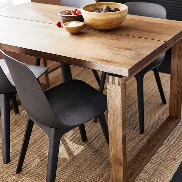 I en spistue med varme farver står et spisebord i træ. Rundt om er der sorte stole.