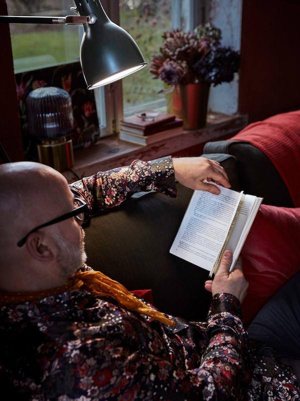 I ett mysigt vardagsrum sitter en man i en soffa och läser en bok. En golvlampa ger bra läsbelysning.