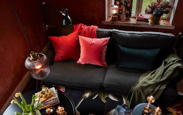 I ett vardagsrum bidrar en mix av taklampa, golv- och bordslampor samt en soffa med färgstarka kuddar till en varm och mysig stämning.