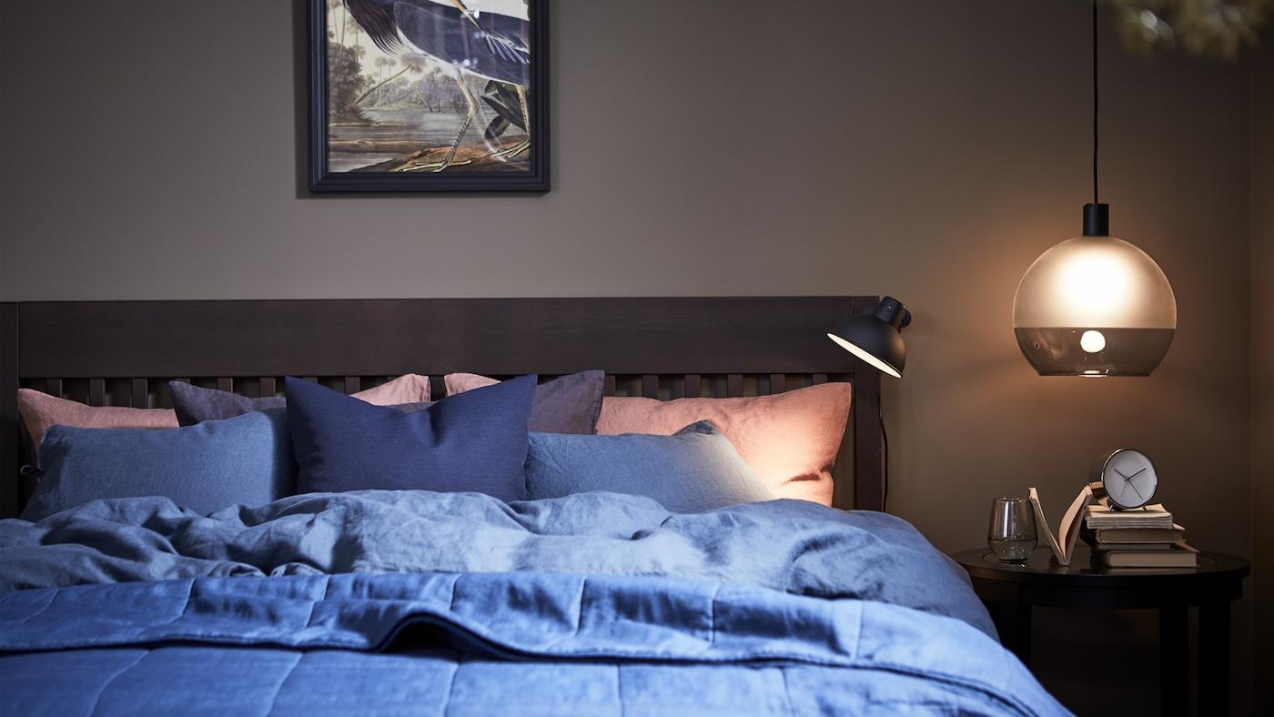 ห้องนอนที่มีแสงไฟสร้างบรรยากาศพร้อมโครงเตียง IDANÄS และปลอกผ้านวมและปลอกหมอน PUDERVIVA/พูเดอร์วีว่า สีน้ำเงิน