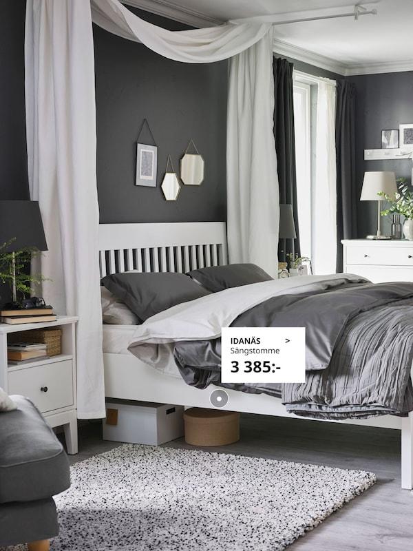 IDANÄS sängstomme i vitt med grå påslakan och IDANÄS sängbord i vitt.