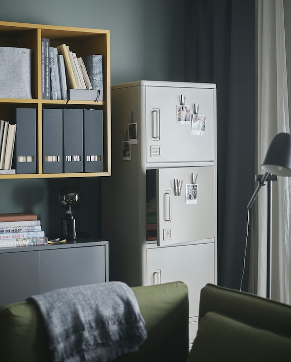 IDÅSEN beige high cabinet with smart locks stands by a wall. Magnetic clips with photos are put on some of the cabinet doors.