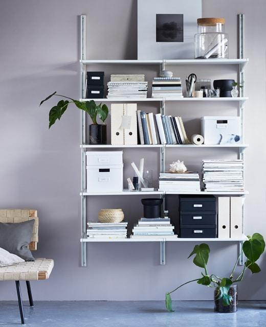 Idées organisation d'une chambre de résidence : étagère contenant images, livres et boîtes de rangement, le tout d'allure très sobre.
