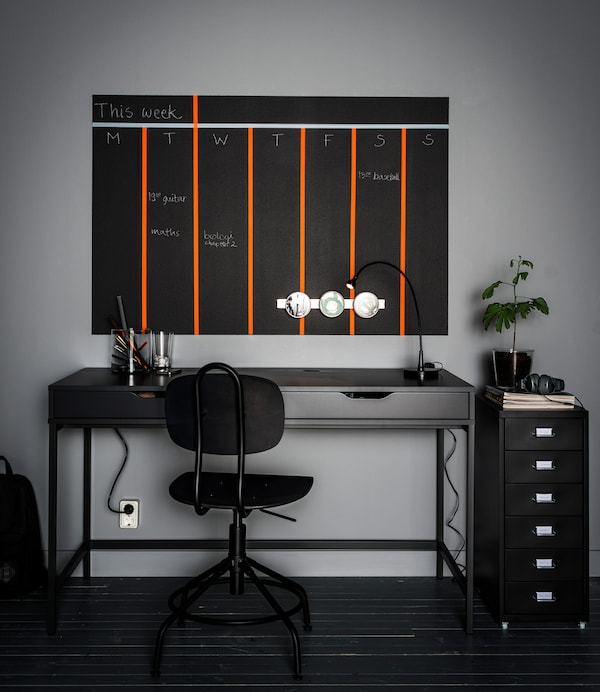 Idées rangement bureau: contenants aimantés et calendrier peint au mur, le tout installé au-dessus d'un bureau gris à deux tiroirs. Sans oublier l'accessoire pour tiroir qui permet de mettre de l'ordre dans les fournitures.