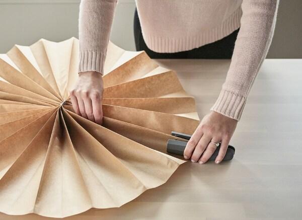 Iemand maakt een grote rozet met als accordeon gevouwen papier en een nietjesmachine.