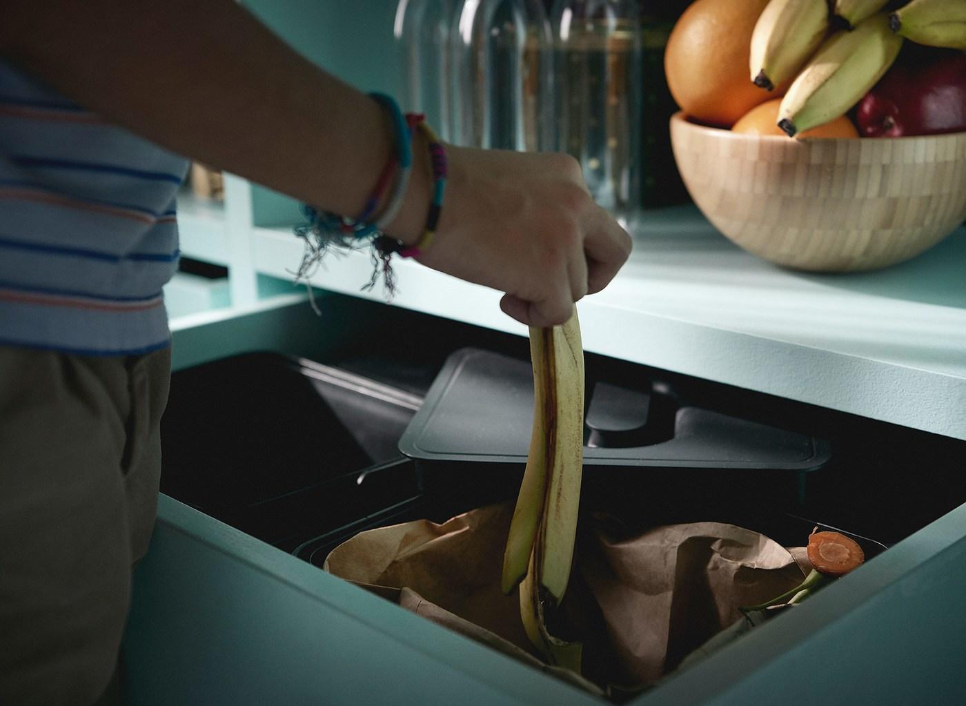 Iemand met armbanden gooit een bananenschil in een IKEA VARIERA afvalscheidingsbak in een keukenlade