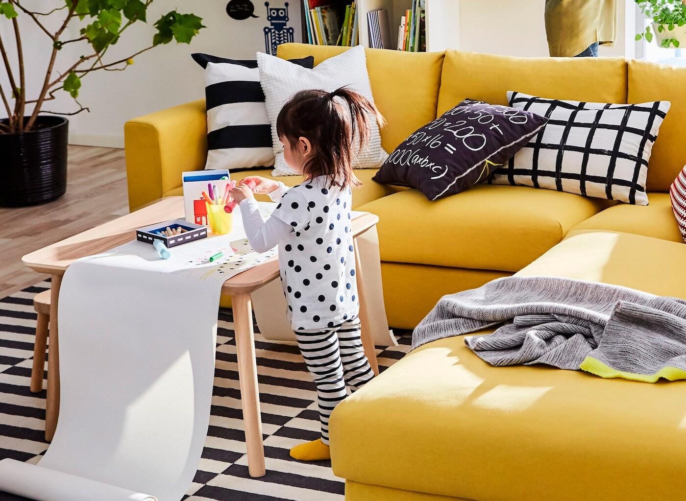 イエローのVIMLE/ヴィムレ 3人掛けソファの横にあるコーヒーテーブルの上に広げた長いロール紙いっぱいに絵を描いている女の子。
