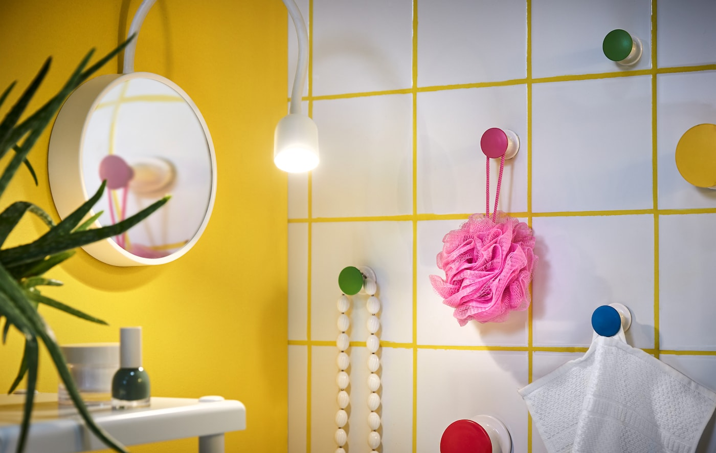 If you are sharing a small bathroom, it's all about finding ways to store your stuff. Use a bare wall and put up hangers to hang your stuff from. These multi-coloured ones called LOSJÖN are easy to attach as they have self-adhesive backing!