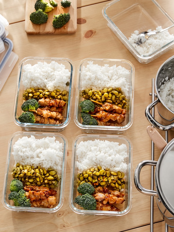 IKEA 365+ glass ramekin dishes full of home cooked food with layers of rice, beans, broccoli and chicken on a countertop.