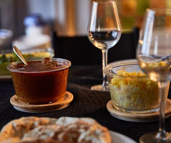 IKEA 365+ -lasiastiat, joissa on bambukannet, jotka on täytetty erilaisilla elintarvikkeilla, ja viinilasit viihtyisässä ympäristössä.