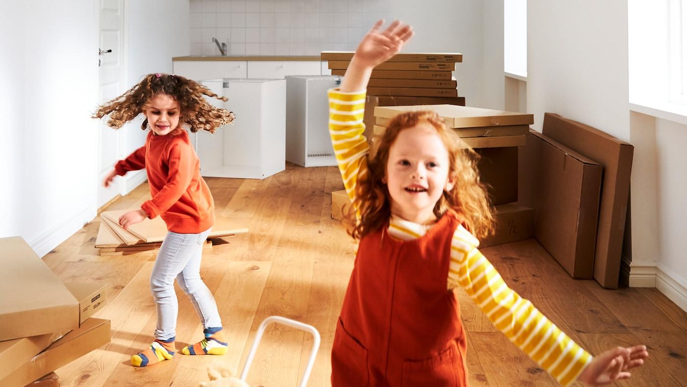 마룻바닥과 화이트 벽만 있는 텅 빈 공간에서 여자아이 두 명이 쌓여 있는 IKEA 플랫팩 제품들 앞에 서있습니다.