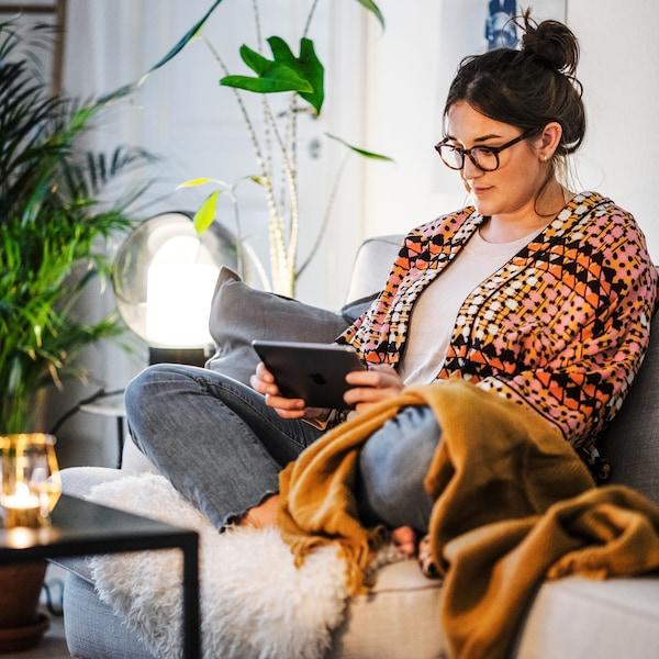 한 여성이 소파에 편히 기대어 앉아 온라인으로 IKEA 전문가가 소개하는 홈퍼니싱에 대해 배우고 있어요.