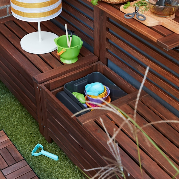 IKEA ÄPPLARÖ dark stained wood storage bench propped open to reveal children's toys.