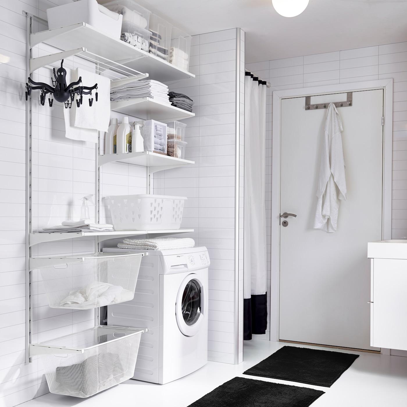 IKEA ALGOT väggskenor och hyllor i vitt i ett annars ljust badrum med svarta detaljer i form av badrumsmatta och duschdraperi.