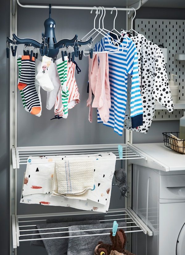 IKEA ALGOT white rails that are hanging towels and sheets. Shirts and socks to dry are above.