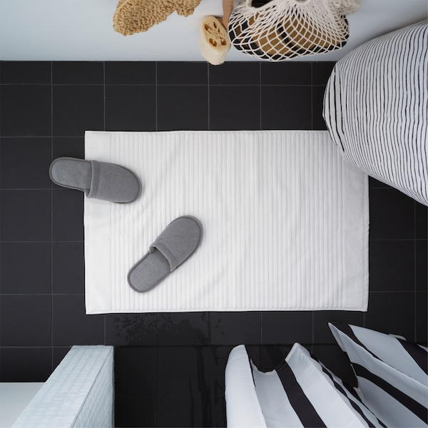 IKEA ALSTERN white bath mat is placed on a black bathroom floor. Gray slippers are placed on the mat.
