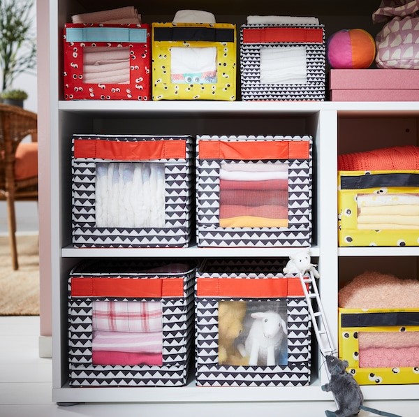 IKEA ANGELÄGEN colourful lidless boxes with transparent fronts in STUVA changing table open storage slots.