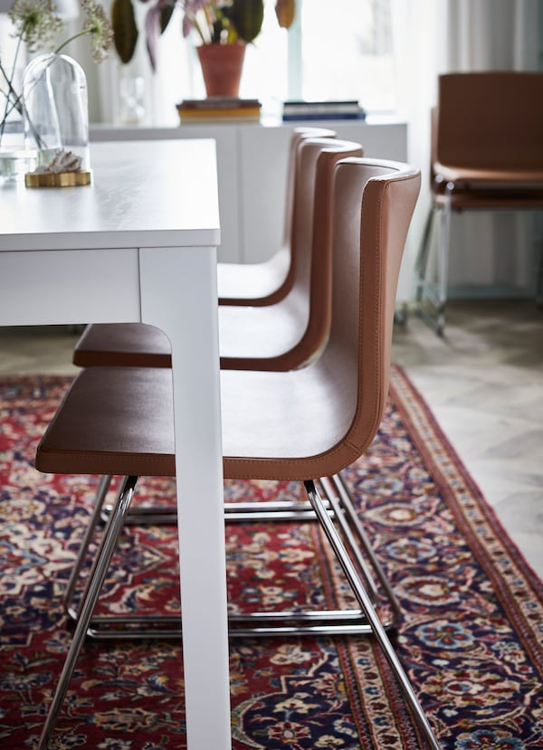 IKEA BERNHARD golden brown leather seats arranged in a line down a white dining table.