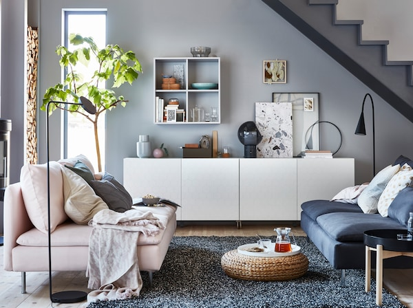 IKEA BESTÅ white closed storage cabinet system with VASSVIKEN honeycomb patterned doors underneath a stairwell, furnished with SÖDERHAMN pink and dark grey two-seater sofas and round YPPERLIG black tray coffee table.